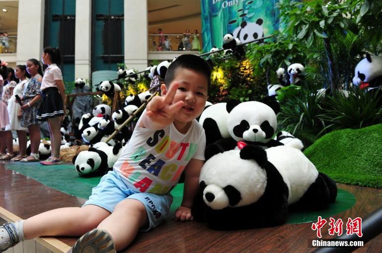 6月26日,众多熊猫玩偶出现在河北石家庄先天下广场,吸引了不少孩子与家长关注。据活动主办方介绍,2014年巴西世界杯主题曲《we are one》我们是一家人唱响全球,人和动物也应该和谐共处。他们希望人们能受到世界杯主题曲的感染,共同保护动物和大自然,并为此准备了1000只布艺大熊猫,用于现场展出和与市民互动。中新社发 翟羽佳 摄 *武汉华中车展中外车模美艳比拼 *