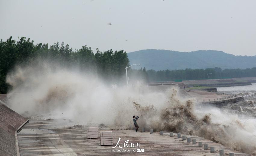 在著名的观潮景区——浙江省海宁市一观潮点,一名摄影工作者为近距离