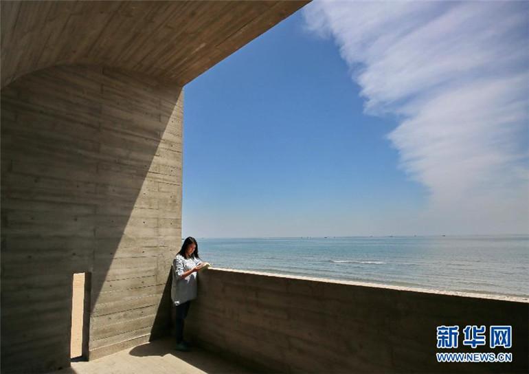 5月14日,一位读者在秦皇岛北戴河新区海边图书馆的露台上阅读.