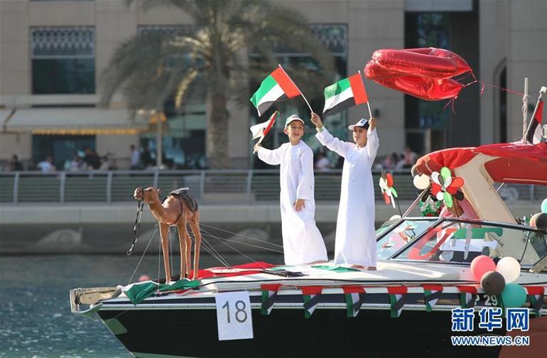 12月2日,在阿联酋迪拜,两名儿童在游艇上挥舞国旗。