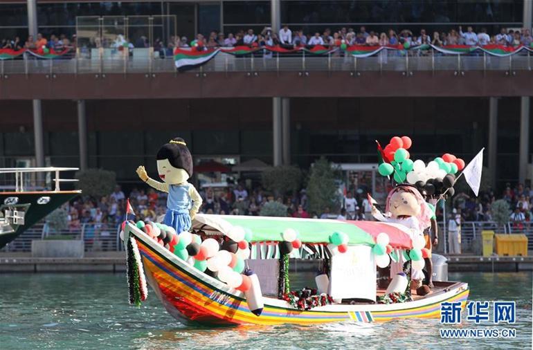 12月2日,在阿联酋迪拜,岸上的人们观看参加游行展示的一艘船艇。