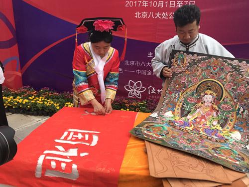 蒙古皮雕画(右一),手撕画表演(左一)